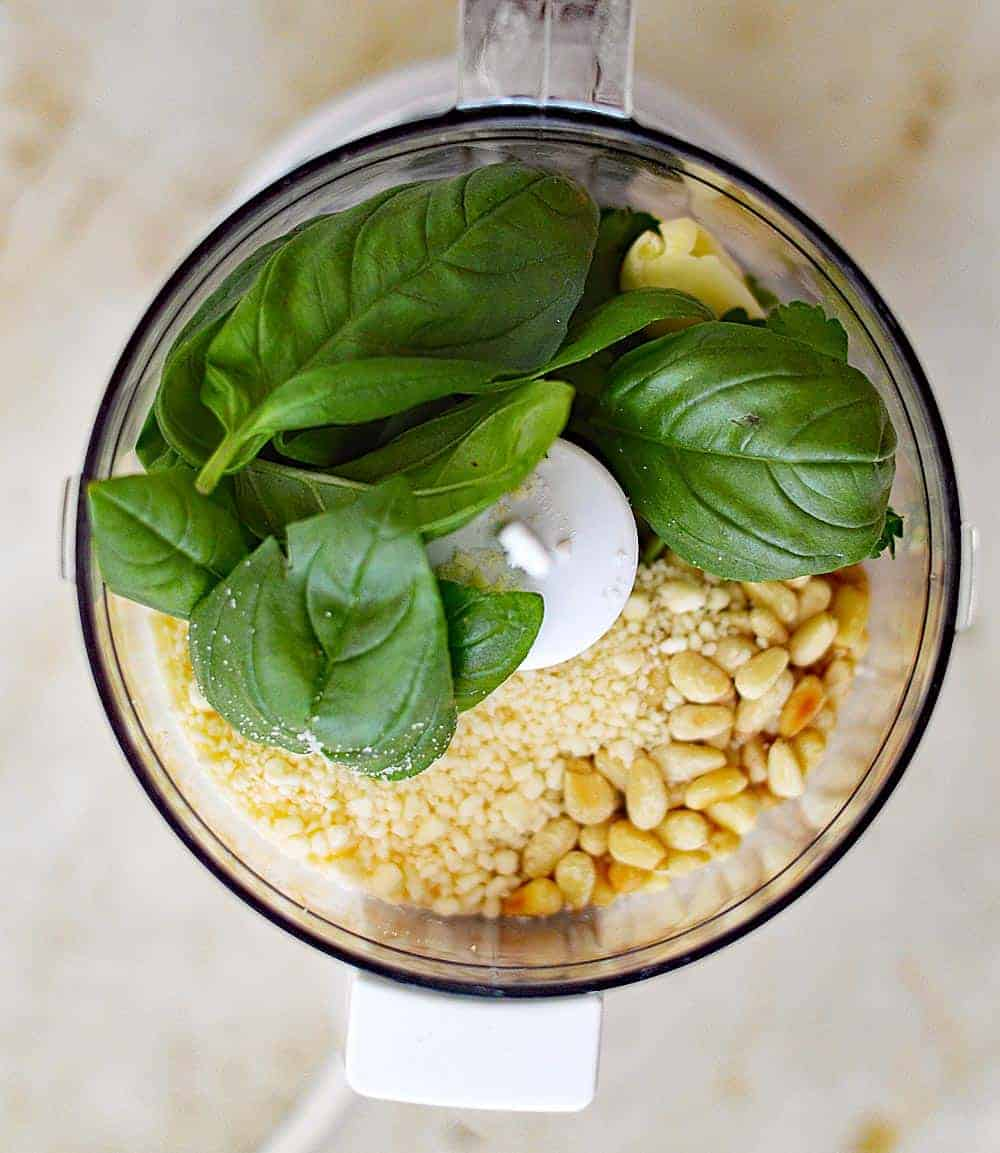 food processor filled with ingredients for basil pesto