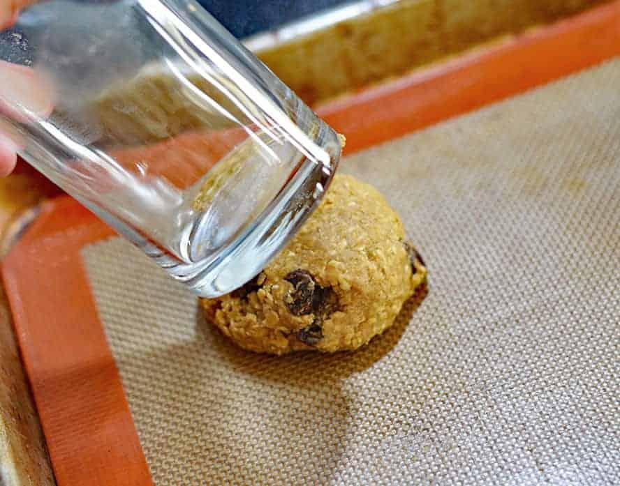 Using a glass to flatten dough for Big & Chewy Vegan Oatmeal Raisin Cookies