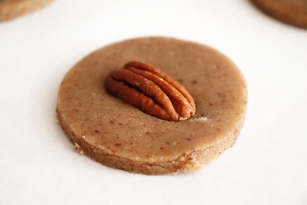Placing a pecan half onto the unbaked cookie