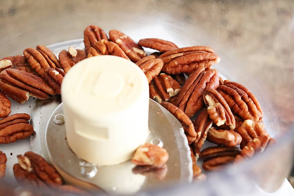 Roasted and cooled pecans in food processor