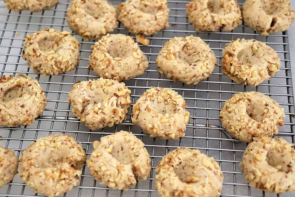 Baked thumbprint cookies on a cooling rack ready for filling