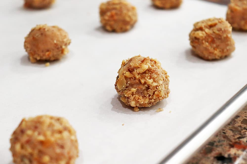 Balls of dough rolled in chopped walnuts on a cookie sheet