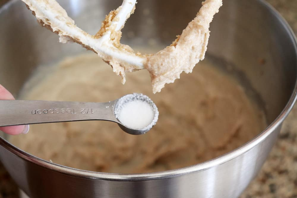 Salt being added to the bowl of an electric mixer