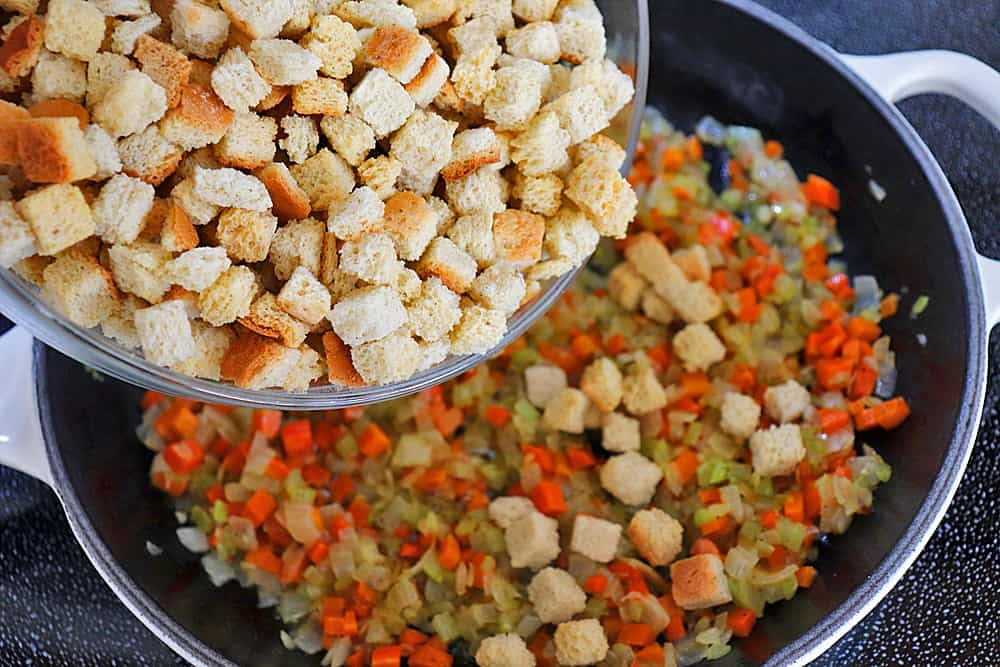 Adding dried bread cubes to the sauteed vegetables in a skillet