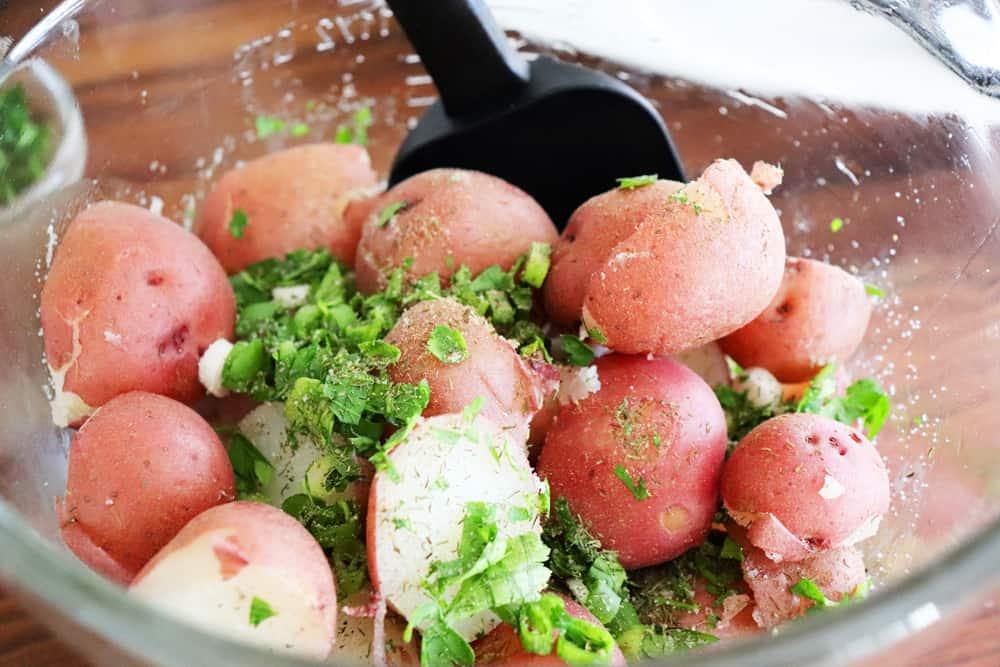 Adding sliced potatoes and herbs to mixing bowl for Warm Potato Salad with Dijon Vinaigrette