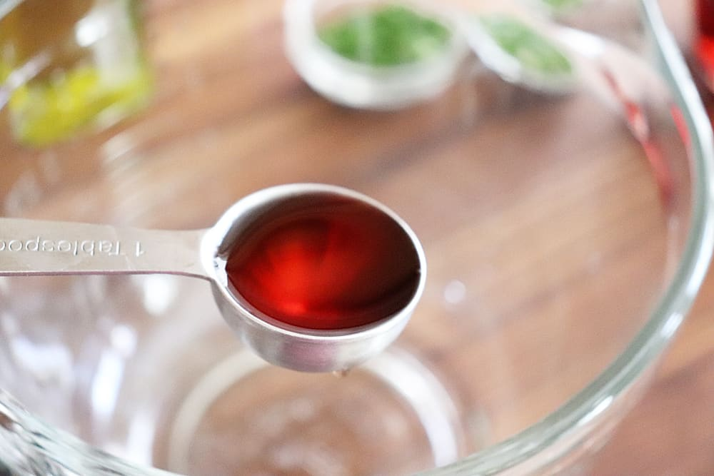 Red wine vinegar in a measuring spoon for Warm Potato Salad with Dijon Vinaigrette