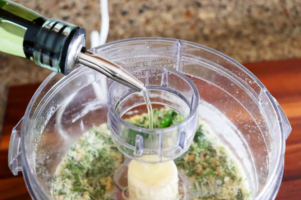 Adding oil to the food processor for Crispy Smashed Potatoes with Parsley Pesto