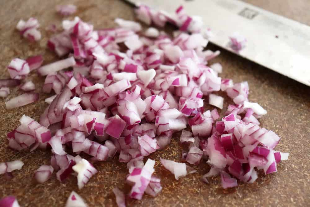 Diced red onion on a brown cutting board with a knife
