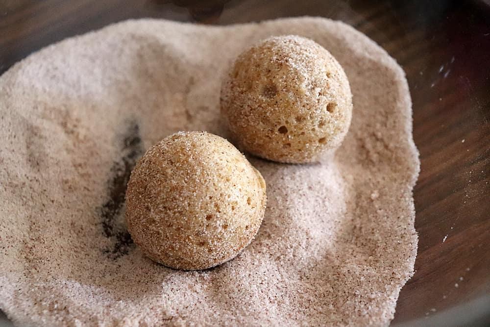 Rolling doughnuts in cinnamon sugar