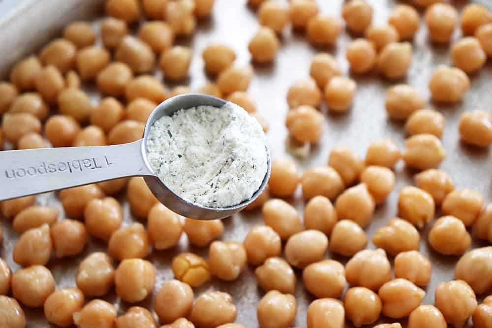 Sprinkling ranch seasoning on the chickpeas