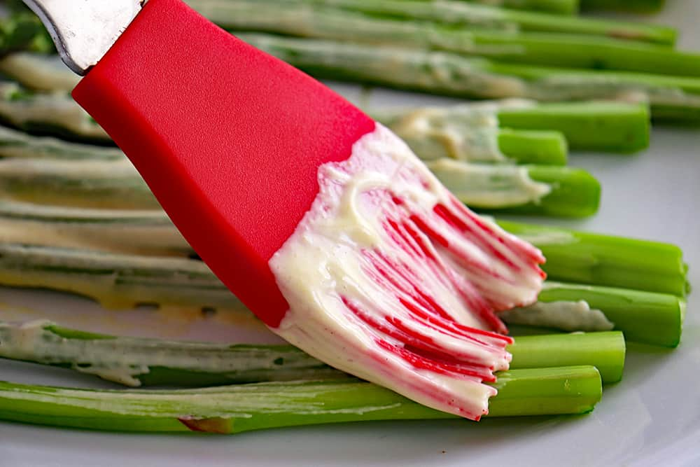 Brushing mayo mixture on asparagus