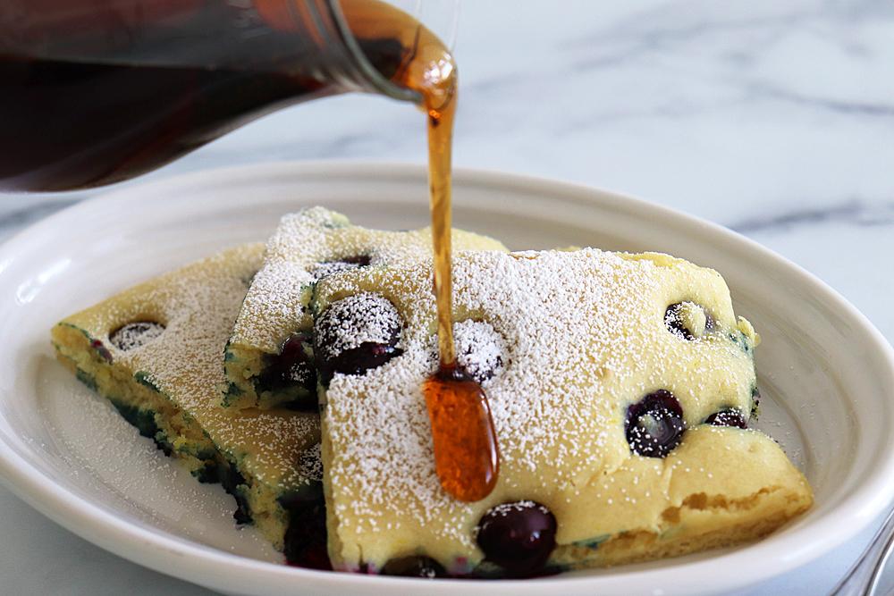 Pouring syrup on Powdered Sugar Vegan Lemon Blueberry Sheet Pan Pancakes