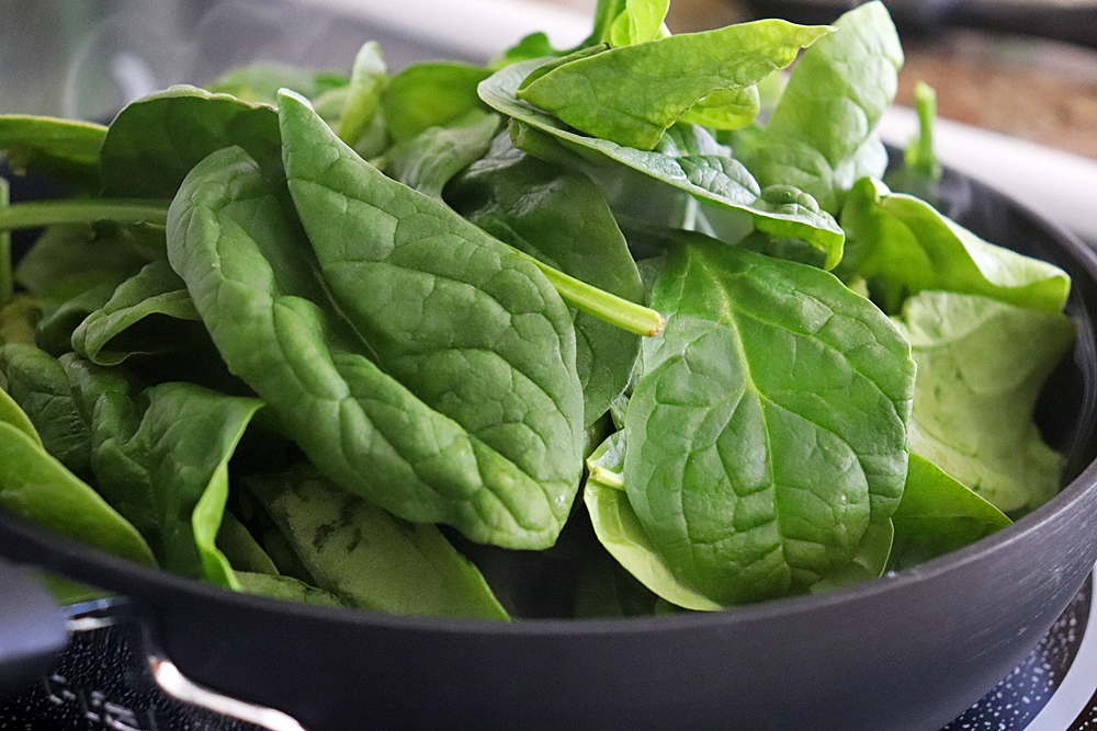 Adding spinach to the saute pan